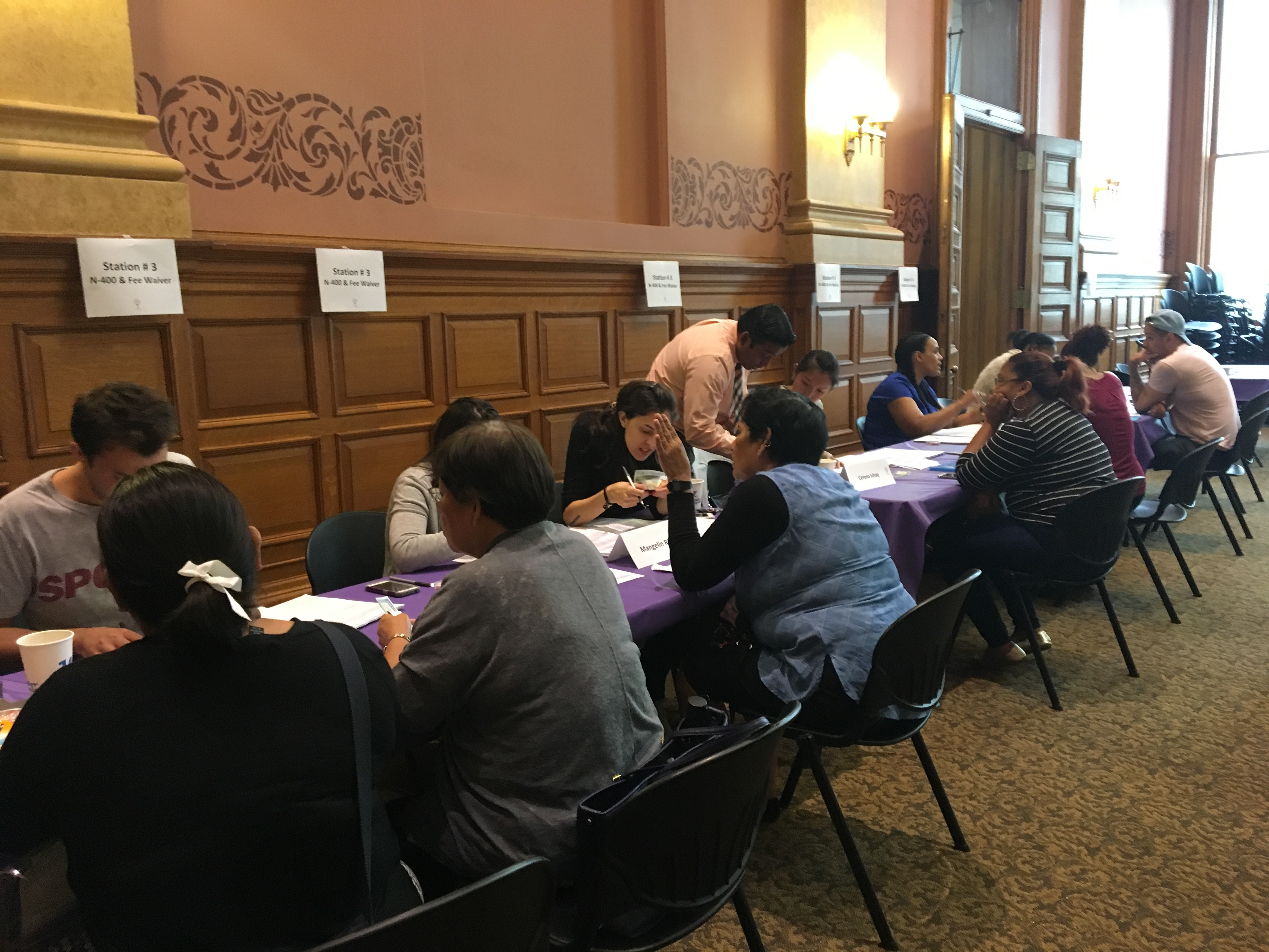 Volunteer lawyers and volunteers from the community assist eligible residents in completing their application for naturalization.
