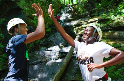 Jersey City teens celebrate after rappelling down a waterfall.  After overcoming the physical challenge of the hike to the waterfall they next have to overcome the mental challenge of rappelling down it.