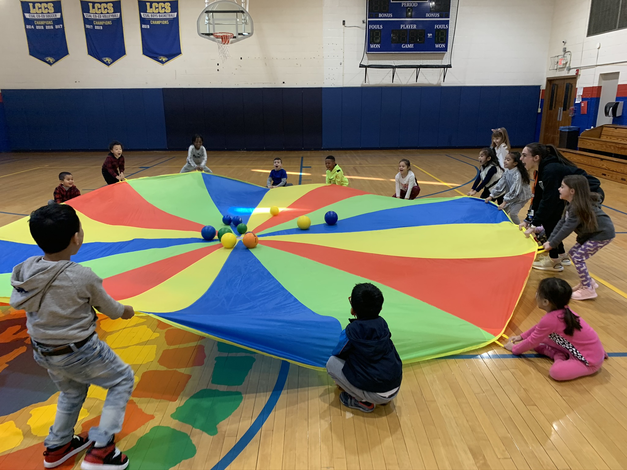 Kindergarten students in gym play with a parachute.
