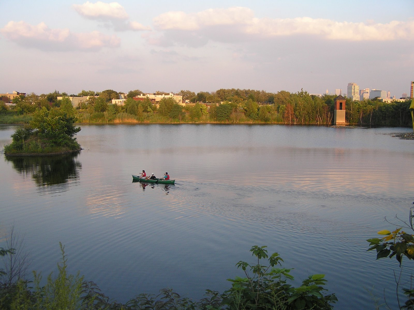Photo overlooking the Reservoir from the West side, facing East. The water, surrounded by green trees, is mostly still and reflecting the sunset and pink clouds. Three people of mixed races are canoeing towards the small island on the left.